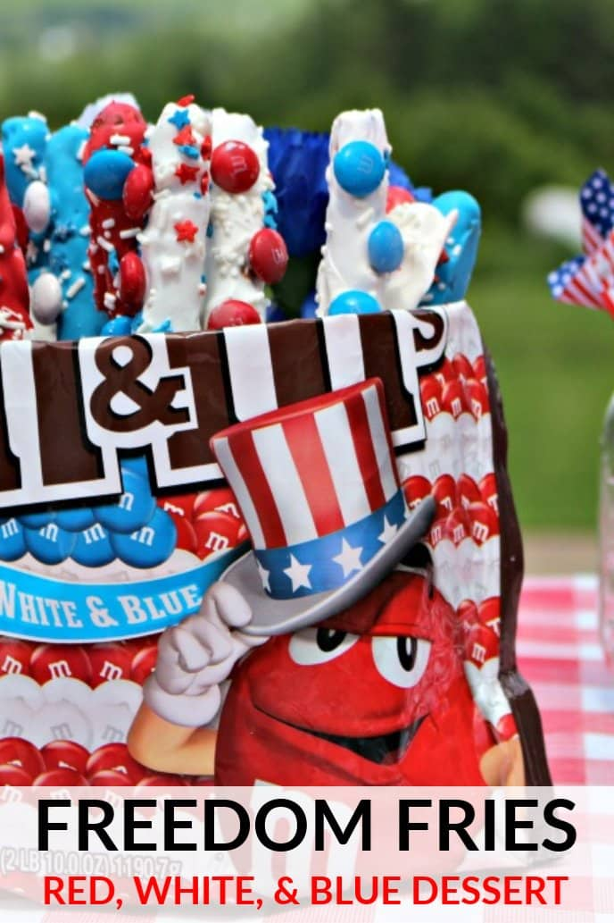 Red, white, and blue dessert for Memorial Day or Fourth of July. Pretzel rods covered in melted red, white, and blue chocolates with candy stick to them, displayed in an M&M's bag.