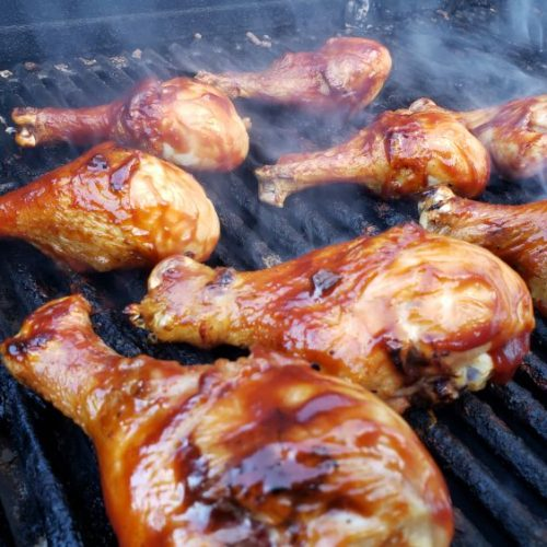 Grill drumsticks on the barbecue grill, several chicken drumsticks cooking on the grill grates.