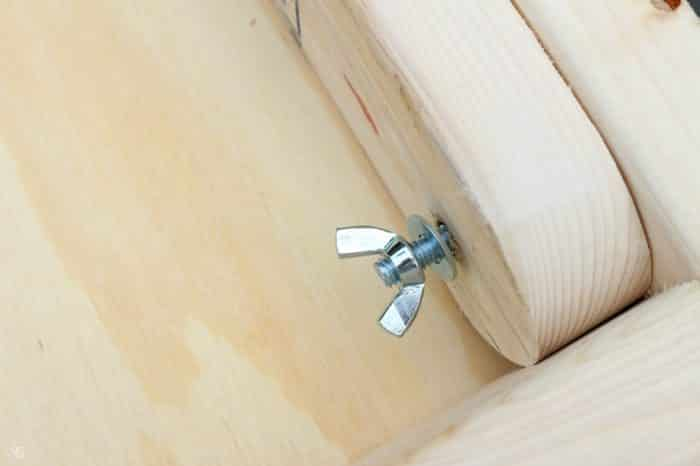 Attaching wooden legs with lag bolts washers and wingnuts.