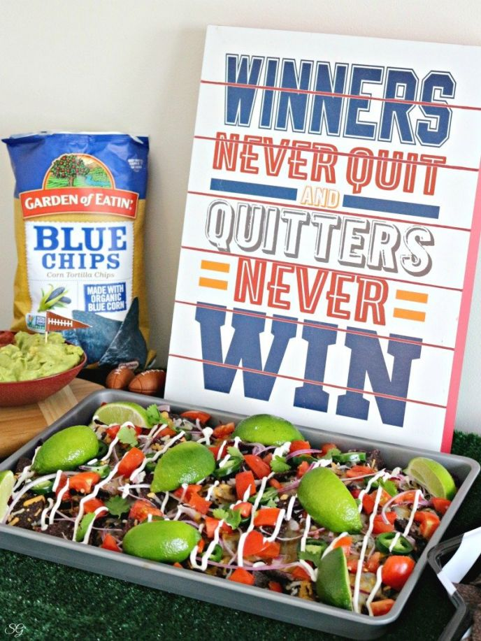 Football party food, nachos with cheese and veggies. Inspirational sign, winners never quit and quitters never win.