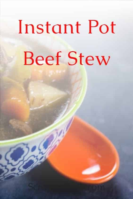 Instant pot beef stew recipe in a bowl with blue design on the outside and an orange spoon sitting next to the bowl.