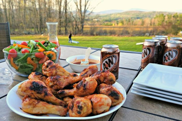 Grilled chicken, salad, A&W root beer on patio table, backyard