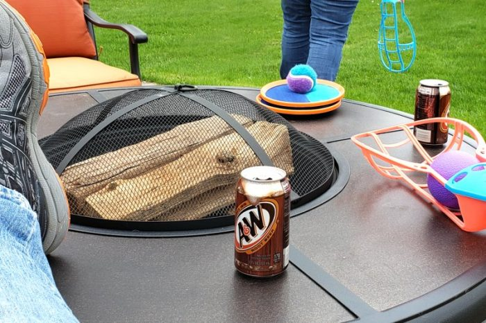 Fire pit table with can of A&W and backyard games