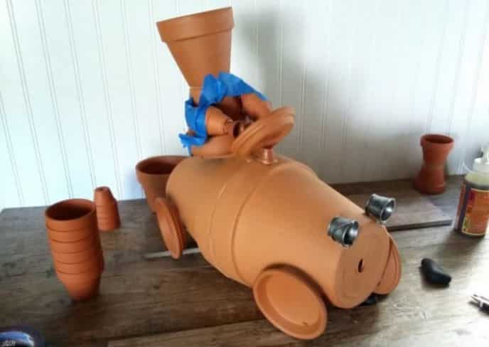 Gluing clay pot race car and driver together.