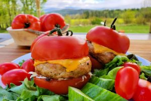 Grilled turkey burgers with cheese placed inside a tomato cut in half for the bun! Great for low-carb diets.