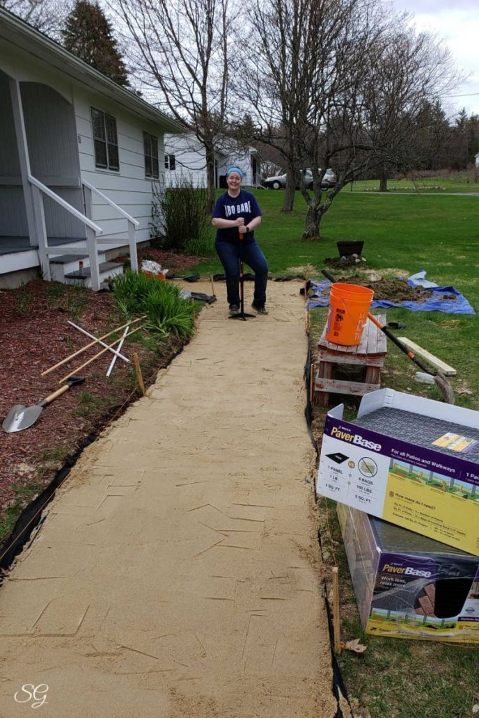 Installing the paver base sand for a DIY paver walkway installation.