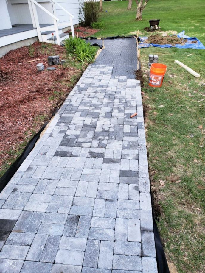 Installing concrete pavers for our DIY walkway.