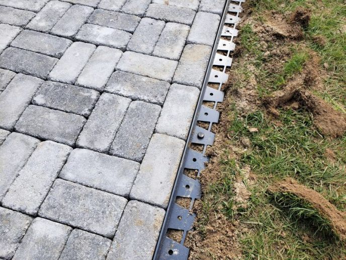 Installing paver edging plastic pieces.