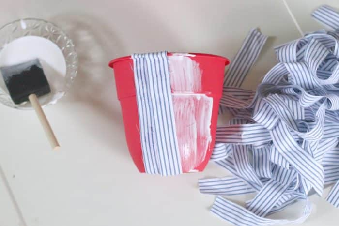Applying fabric to flower pot with men's dress shirts.