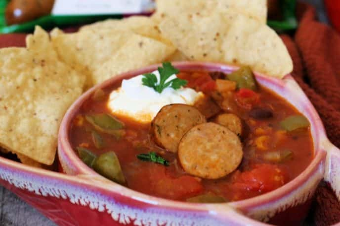Easy chicken taco soup recipe, served in a bowl with sour cream and tortilla chips on the side.