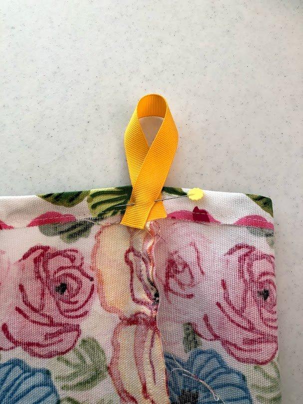 Plastic bag dispenser ribbon hanger