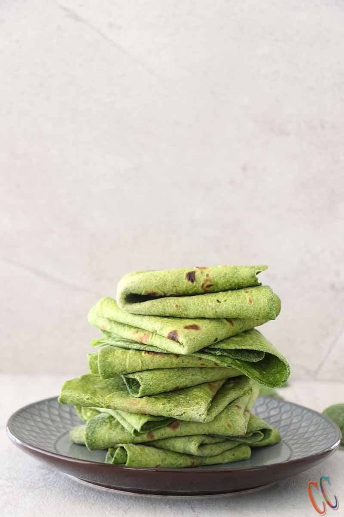 Spinach vegan tortillas, green colored tortillas folded and stacked on a plate