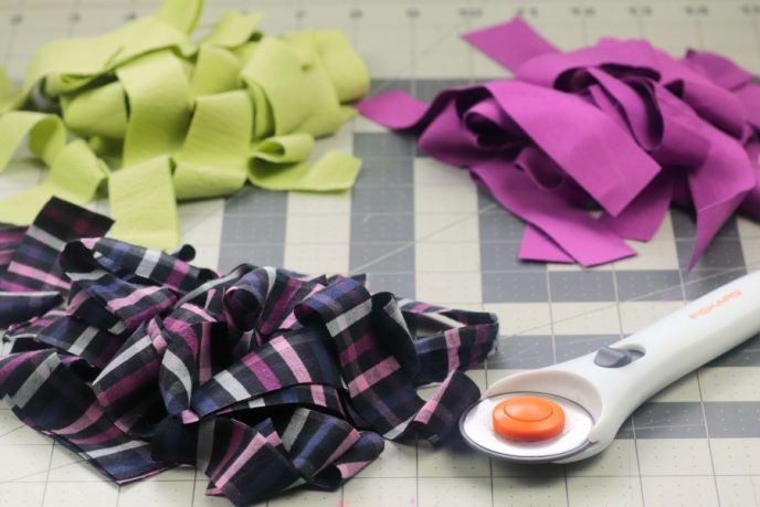 Cutting fabric into strips to create mason jar craft vases.