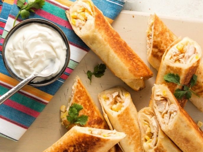 Chicken taquitos recipe, easy baked in the oven or fried in oil, plated and served with sour cream and salsa.