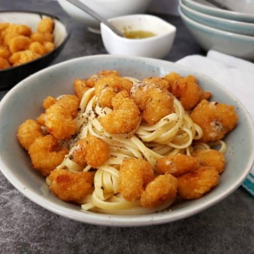 Pasta with popcorn shrimp on top in a bowl