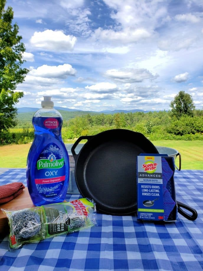 How To Clean A Rusty Cast Iron Skillet, stainless steel scrubbing pads, scrubbing dot sponges, Palmolive dish soap, and cast iron skillet on a table with mountains in background