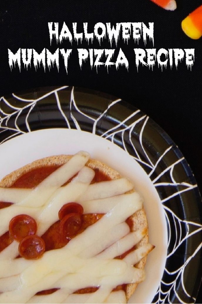 Mummy pizzas for Halloween, round crust, cheese strips for bandages, pepperoni eyeballs, served on a black and white spiderweb themed plate