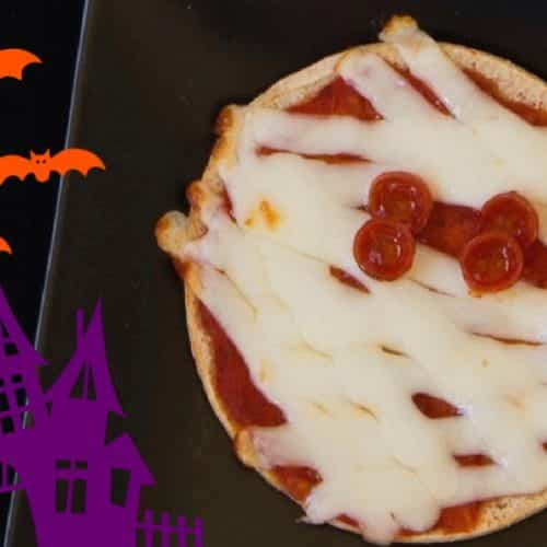 Spooky mummy pizza for Halloween with pizza dressed like a mummy with cheese and pepperoni, a spooky house with bats flying overhead