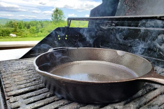 Cast iron skillet on grill being seasoned with oil, grill is open with mountains in the background