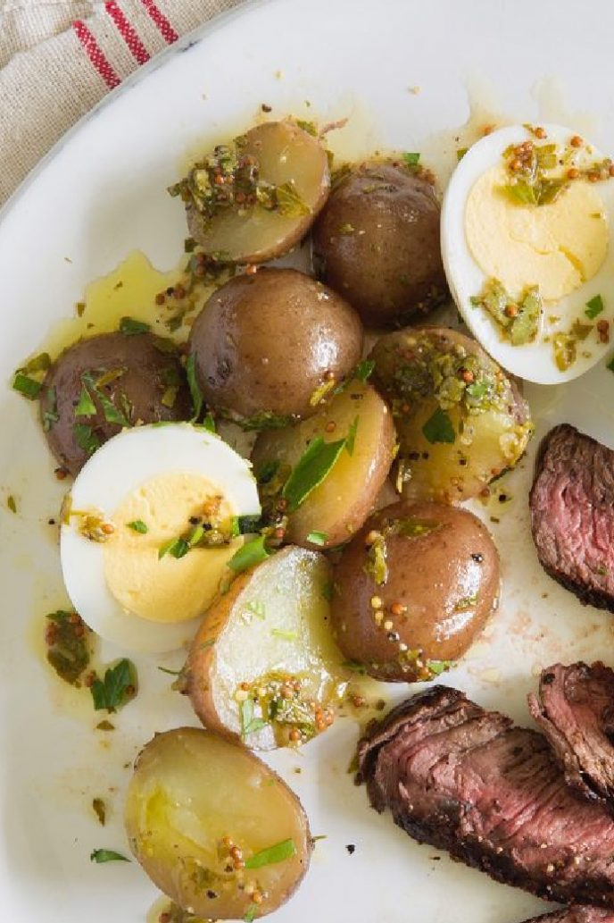 Potatoes and eggs side dish on a plate with steak