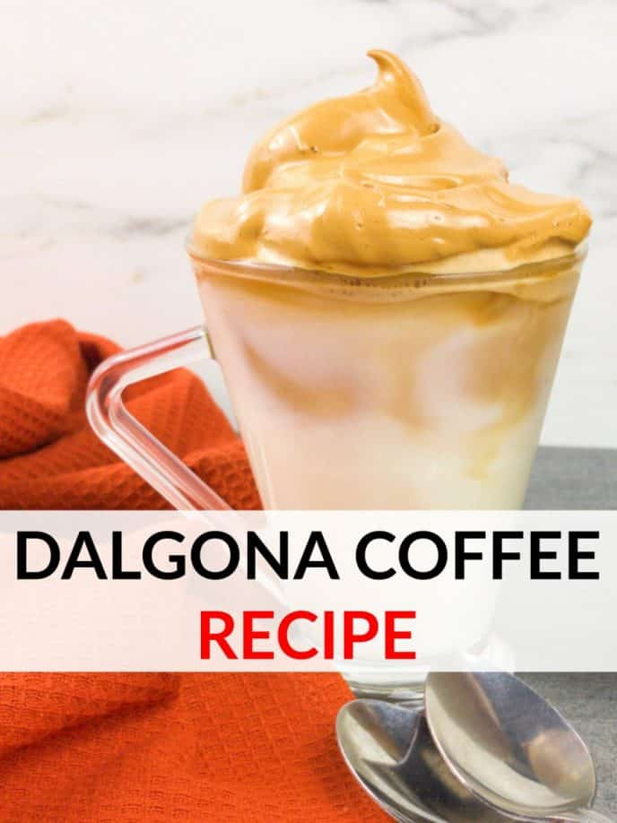 Dalgona coffee recipe. Whipped coffee on top of delicious creamer with ice in a clear mug next to an orange towel with spoons on the table, too.