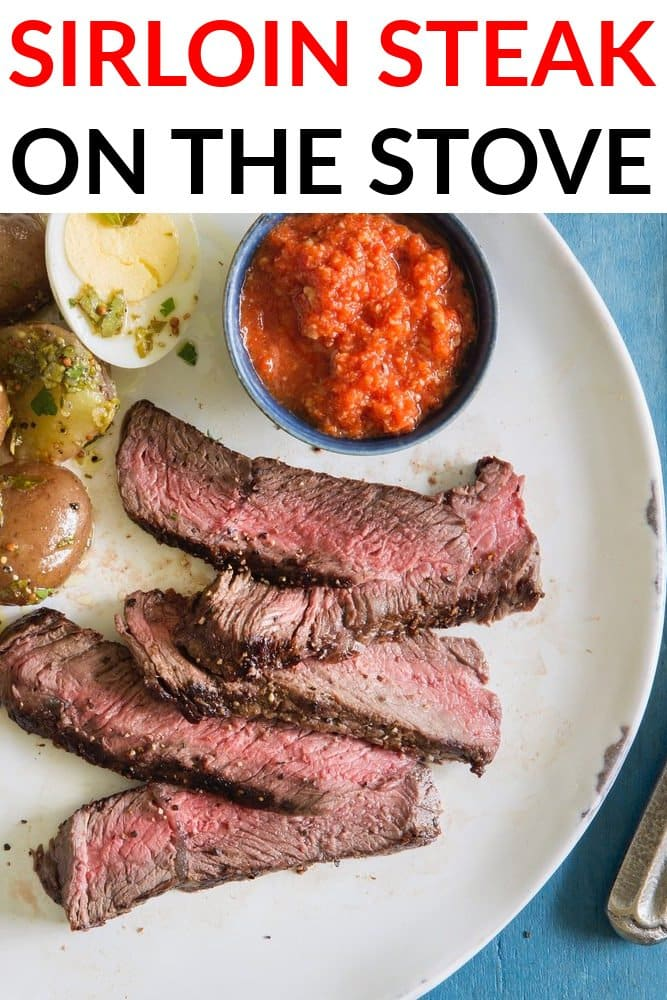 Sirloin steak cook on the stove plated on a white plate with potatoes, eggs, and romesco sauce