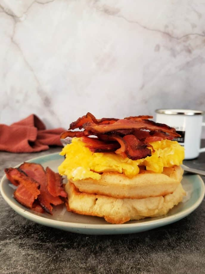 Bacon, egg, and cheese stacked on two waffles with a side of bacon