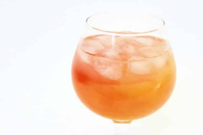 Lemonade cocktail recipe made with juices, in a glass with ice, white background
