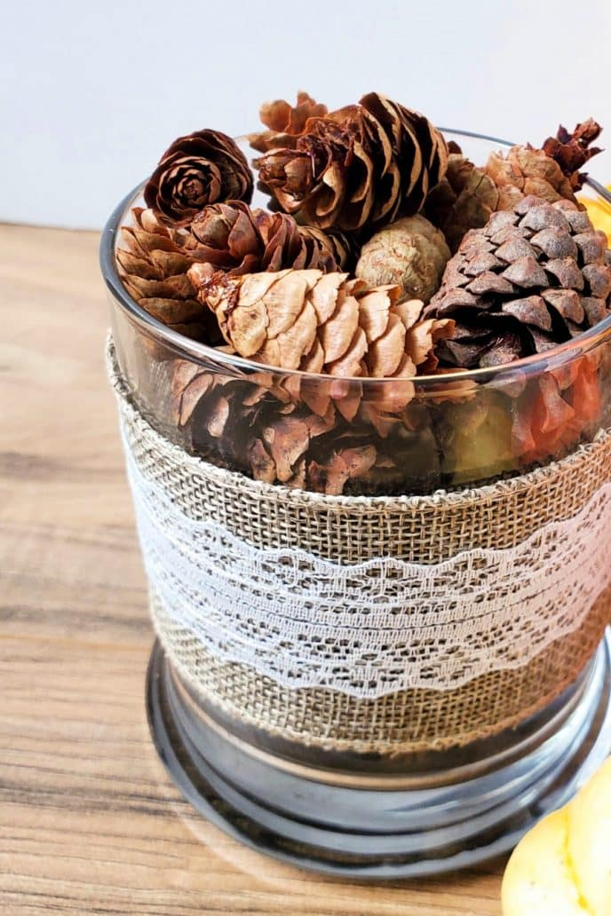 Pine cone craft project, finished project with glass jar wrapped in burlap filled with pine cones.