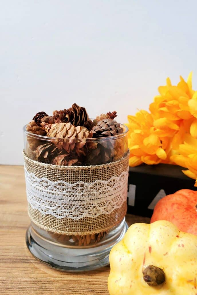 Pine cone craft decor, pine cones in a glass jar wrapped in burlap sitting next to pumpkins and fall flowers