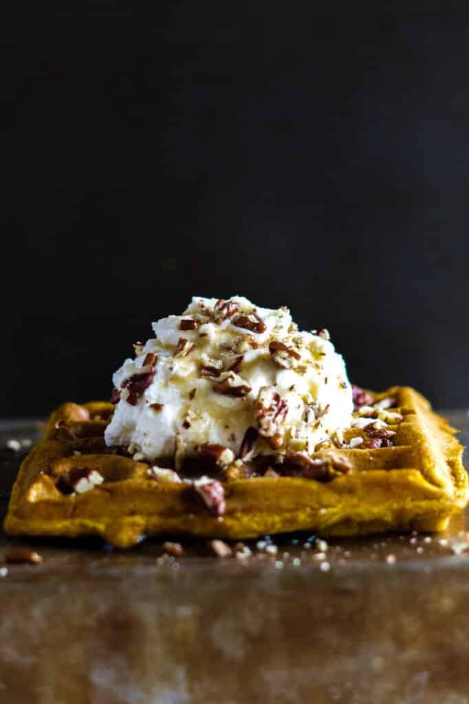 Pumpkin spice waffles topped with whipped cream, chopped pecans, and drizzled with maple syrup.