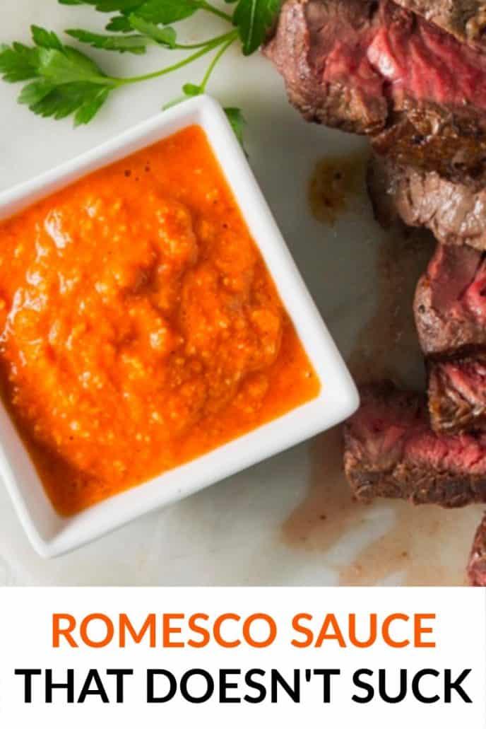 Orange colored romesco sauce served with steak