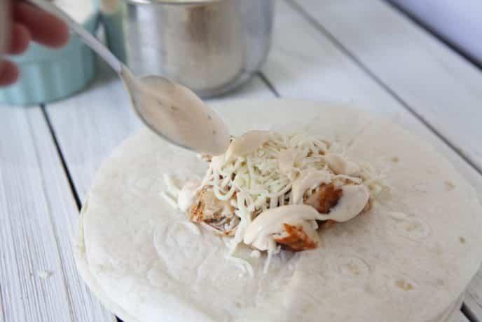 Adding sriracha to chicken wrap