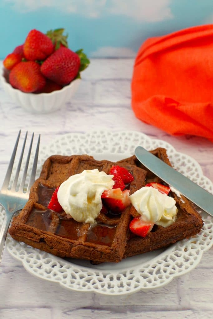 Chocolate Belgian waffles with whipped cream and strawberries on a plate flanked by a knife and fork with a bowl of strawberries in the background