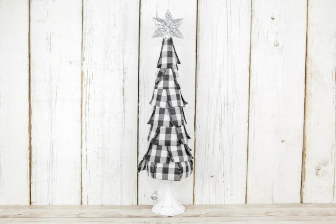 Star on top of DIY Christmas tree craft made using buffalo plaid ribbon, a foam cone, and a candlestick holder.