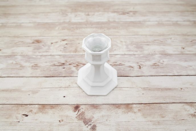 Applying third coat of paint to glass candlestick holder to cover it completely with white paint.