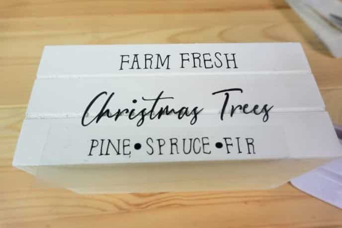 Aligning the Cricut Christmas design onto crate before adhearing it.