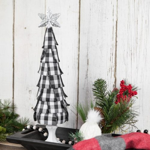 Buffalo plaid Christmas decoration, black and white buffalo plaid ribbon tree on a white tree stand, flanked by decorations like holly and twigs.