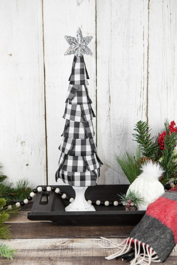 buffalo plaid Christmas decoration tree for a mantel or table centerpiece, black and white buffalo plaid ribbon with a white candlestick tree stand and a silver star on top, this is a DIY project craft