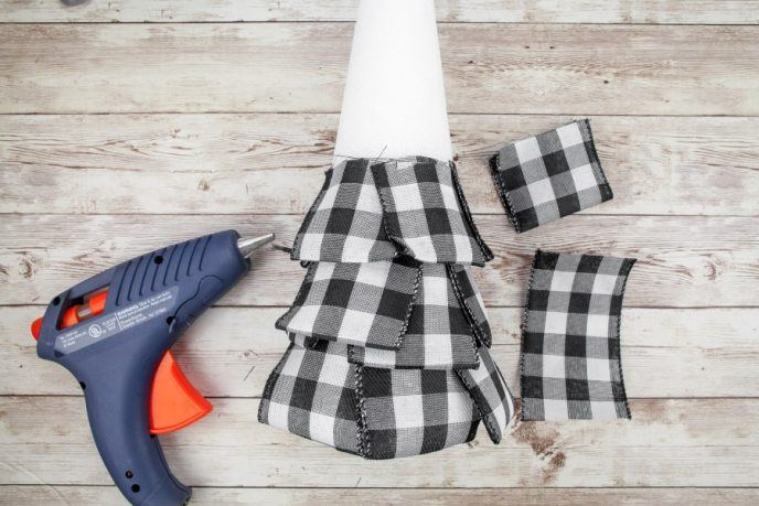 Attaching buffalo plaid ribbon to the middle area of a foam cone to create a Christmas tree decoration