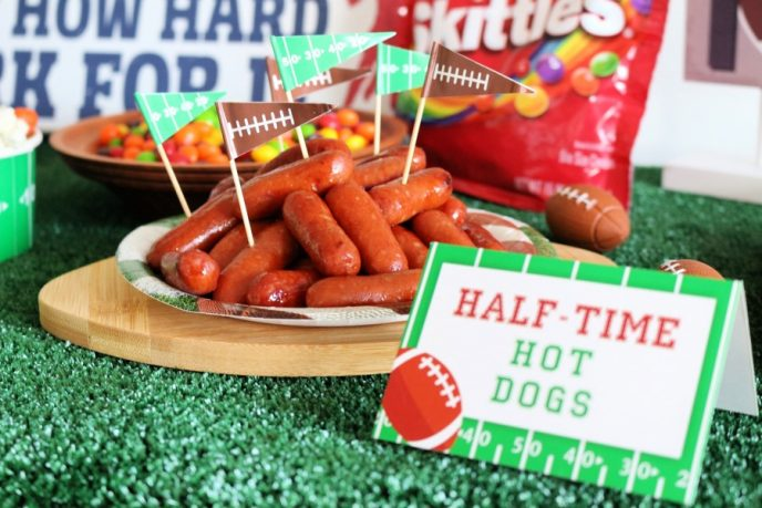 """Cocktail franks on a football plate with football yard line skewers and a football themed sign in front reading """"Half Time Hot Dogs""""."""