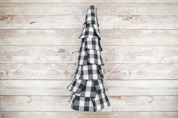 Ribbon covering foam cone to create buffalo plaid Christmas decoration