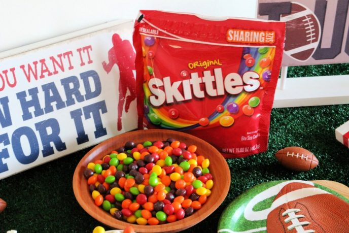 Skittle football party snack in a bowl with the skittles bag behind it.