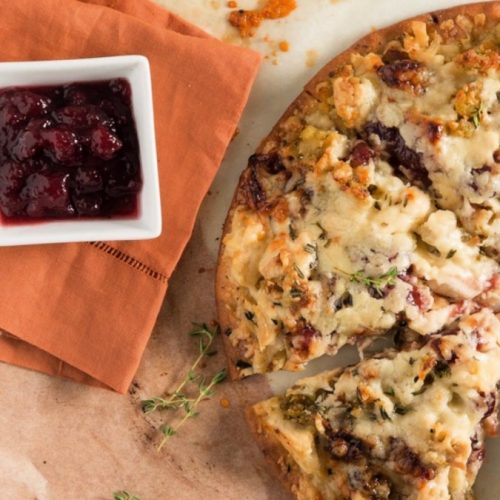 Turkey pizza made with leftover Thanksgiving food like turkey, cranberry sauce, and more.