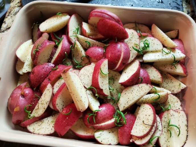 Red potatoes seasoned with salt, pepper, and rosemary, ready to be roasted.