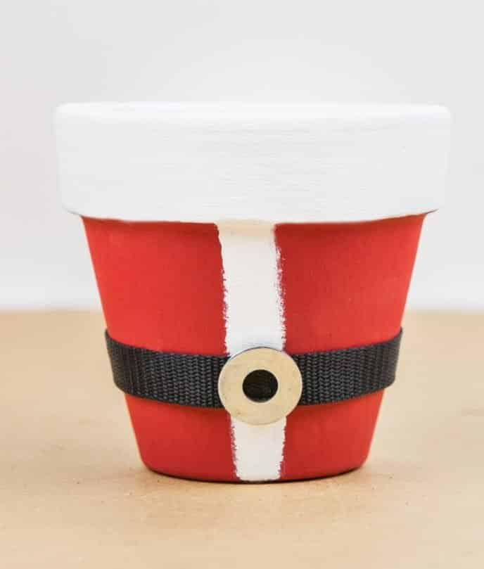Attaching belt to red and white clay pot to make Santa themed gift for neighbors