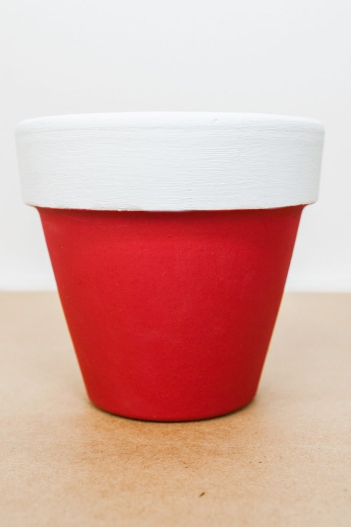 Painting the rim of a clay pot white to create a Santa Clause design