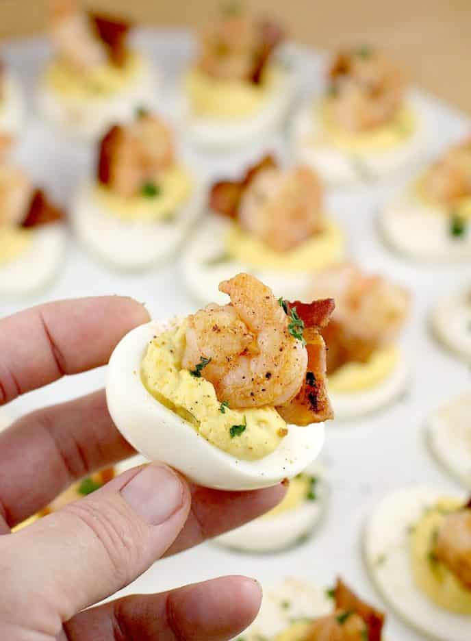 Creole shrimp deviled eggs recipe, eggs, cut in half, mixed yolk, topped with shrimp and bacon being held in hand for the photo