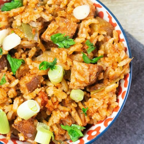 Easy baked jambalaya recipe for dinner at home, served in a dish, dish sitting on blue cloth napkin
