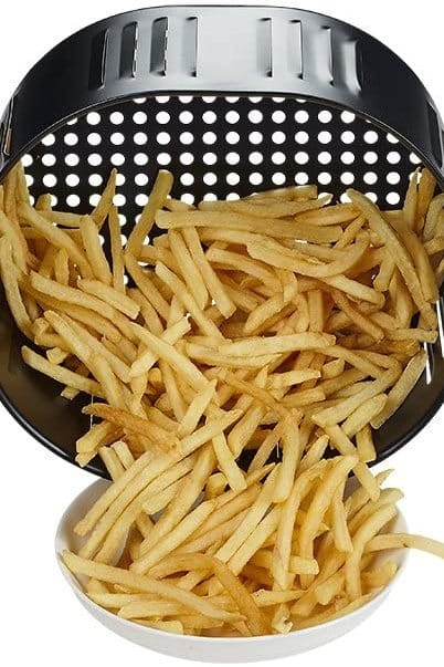 French fries in air fryer basket being poured into a serving bowl.